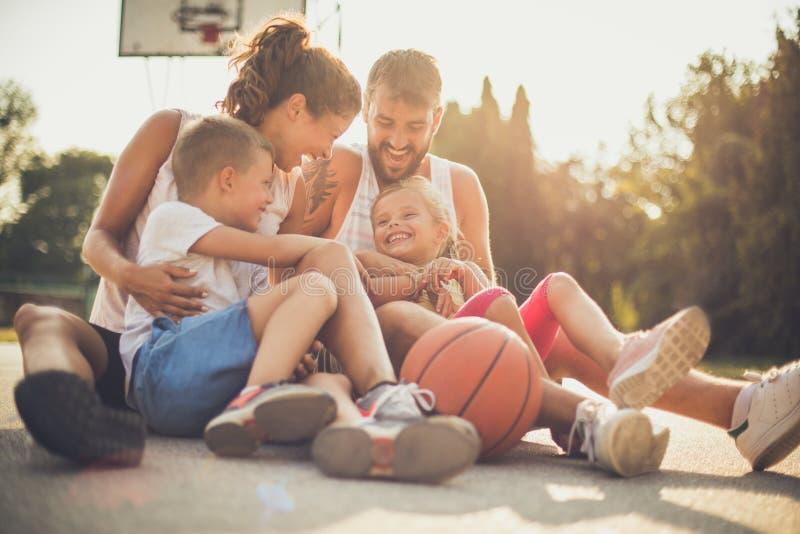 Gelukkige familie bij basketbalspeelplaats stock foto's
