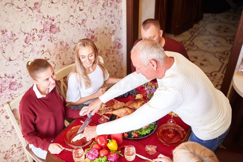 Gelukkige familie bij de dinerlijst het vieren Dankzegging op een vage achtergrond Traditioneel Dankzeggingsconcept stock foto's
