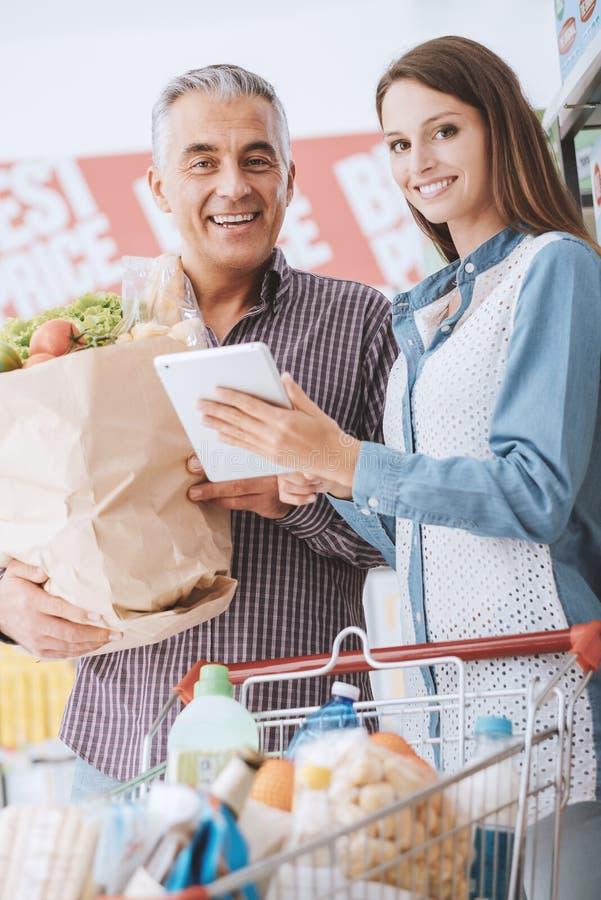 Gelukkige familie bij de supermarkt stock fotografie