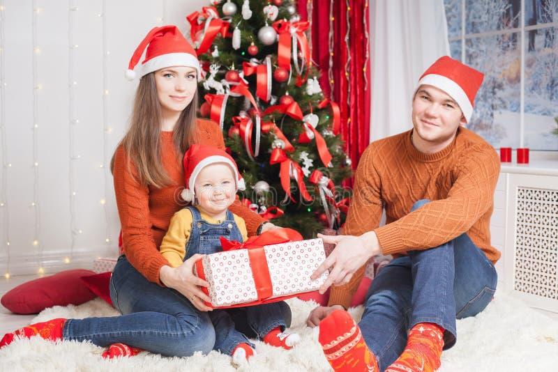 Gelukkige familie bij de zitting van de Kerstmisvooravond samen dichtbij verfraaide boom royalty-vrije stock foto