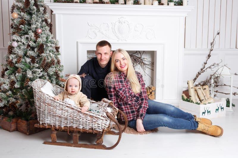 Gelukkige familie bij Kerstmis De ouders en de babyzitting op de vloer en het glimlachen stock afbeelding