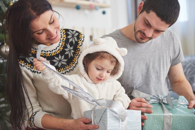 Gelukkige familie bij Kerstmis in ochtend het openen giften samen dichtbij de spar Het concept familiegeluk en goed royalty-vrije stock afbeelding