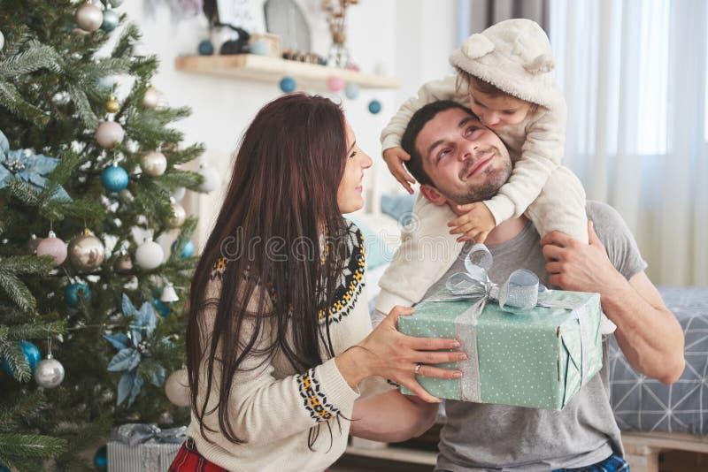 Gelukkige familie bij Kerstmis in ochtend het openen giften samen dichtbij de spar Het concept familiegeluk en goed stock afbeeldingen