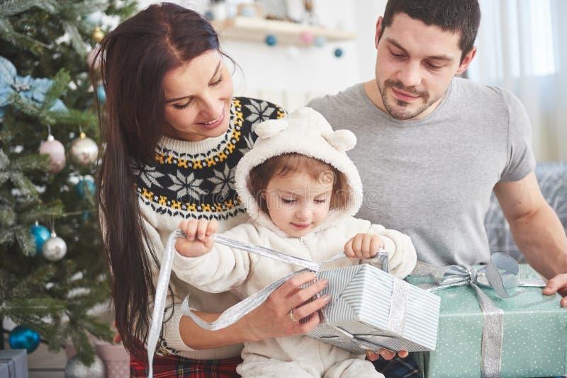 Gelukkige familie bij Kerstmis in ochtend het openen giften samen dichtbij de spar Het concept familiegeluk en goed royalty-vrije stock fotografie