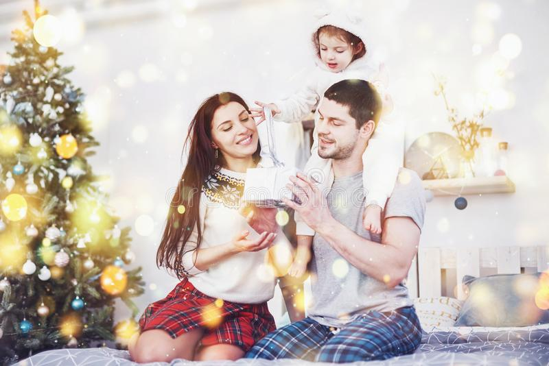 Gelukkige familie bij Kerstmis in ochtend het openen giften samen dichtbij de spar Het concept familiegeluk en goed stock fotografie
