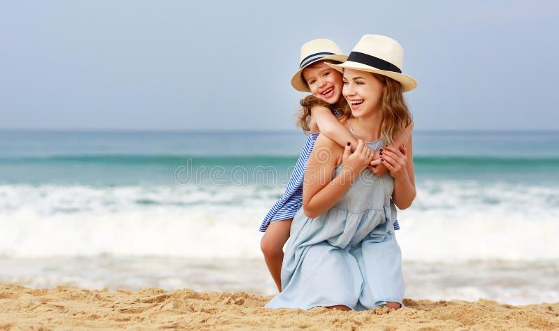 Gelukkige familie bij strand moeder en kinddochteromhelzing op zee stock afbeeldingen