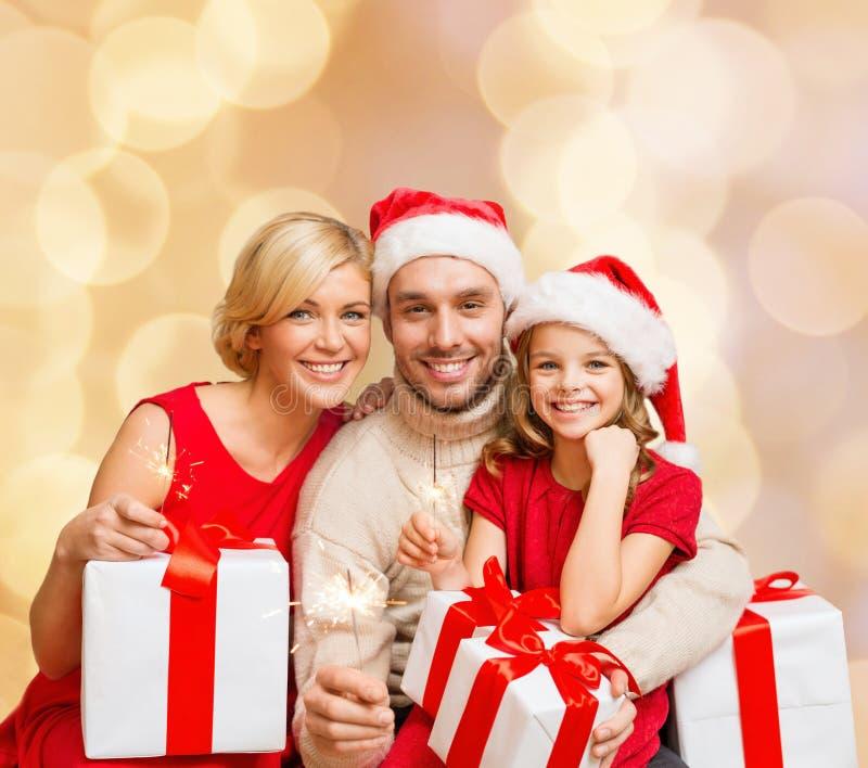 Gelukkige familie in de hoeden van de santahelper met giftdozen stock foto's