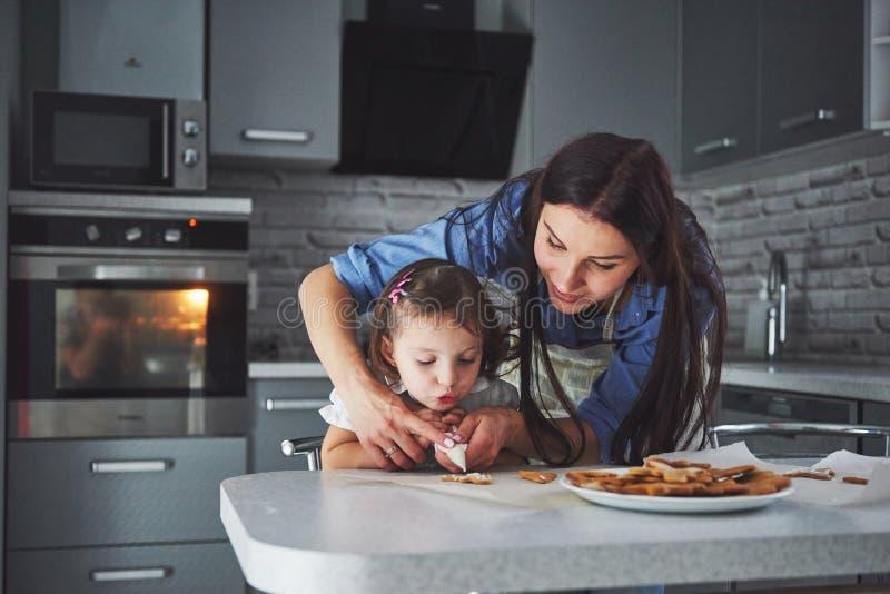 Gelukkige familie in de keuken Het concept van het vakantievoedsel De moeder en de dochter verfraaien koekjes Gelukkige familie i stock foto