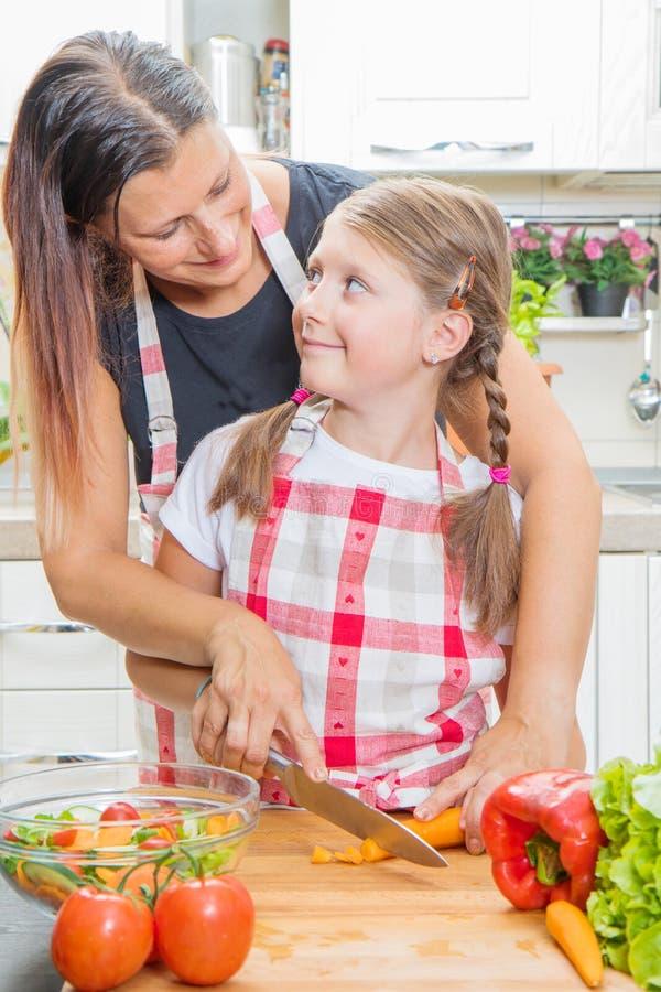 Gelukkige familie in de keuken Moeder en kind de dochter bereidt de groenten voor royalty-vrije stock foto's