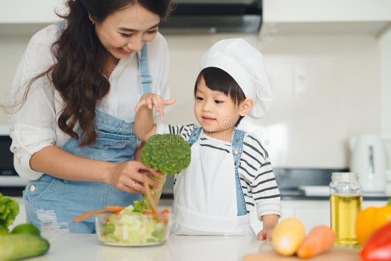 Gelukkige familie in de keuken Moeder en kind de dochter is prepa stock afbeeldingen