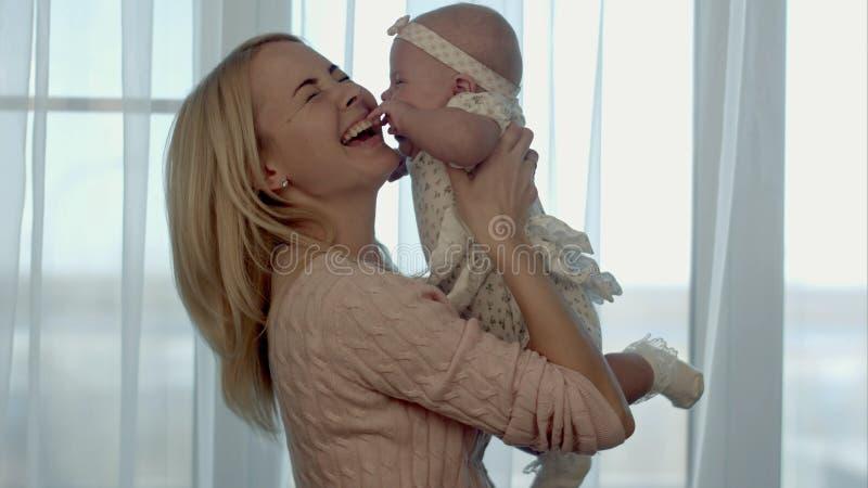 Gelukkige Familie De moeder werpt omhoog en kussende baby royalty-vrije stock afbeelding
