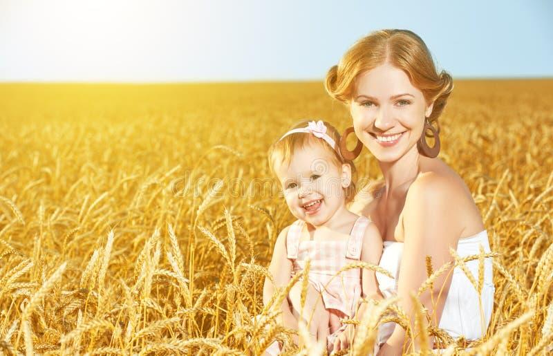 Gelukkige familie in de zomeraard Moeder en babydochter op het tarwegebied stock afbeeldingen