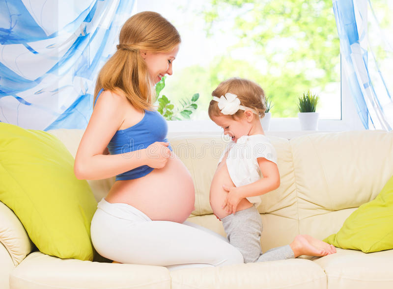 Gelukkige Familie De zwangere moeder en babydochter die pret hebben ontspant