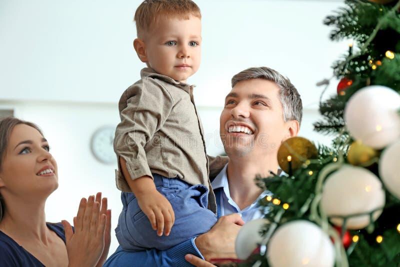 Gelukkige familie dichtbij Kerstboom thuis stock fotografie