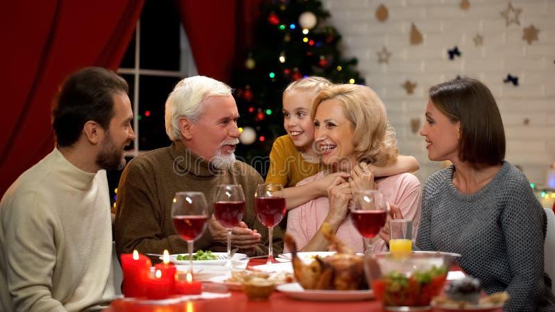 Gelukkige familie die bij Kerstmisdiner babbelen die grappige verhalen, meisje vertellen die oma koesteren royalty-vrije stock afbeelding