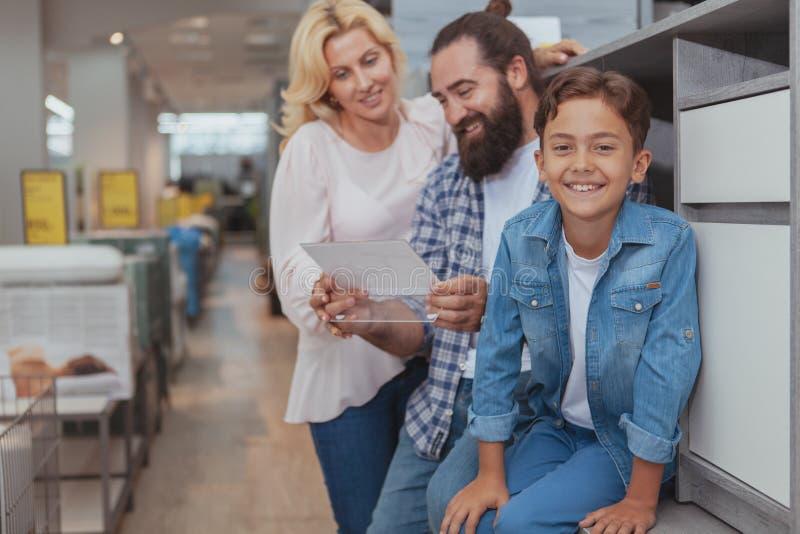 Gelukkige familie die bij meubilairopslag winkelen stock afbeeldingen