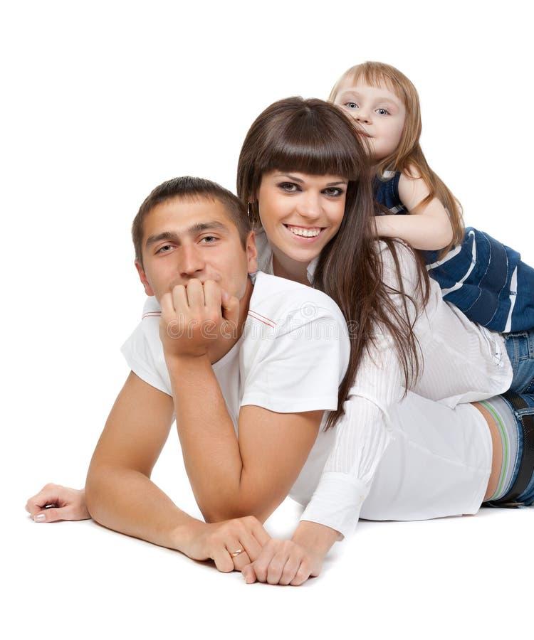 Gelukkige familie die de camera op hun vloer bekijkt royalty-vrije stock afbeeldingen