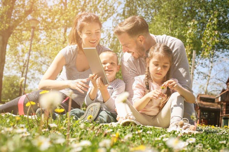 Gelukkige familie die digitale tabletzitting op het groene gras gebruiken FA royalty-vrije stock foto's