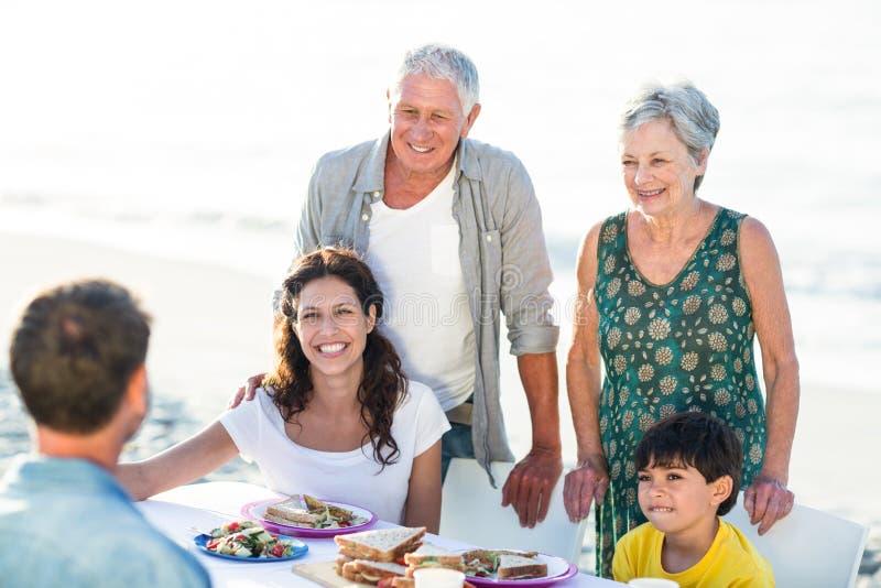 Gelukkige familie die een picknick hebben bij het strand stock foto's
