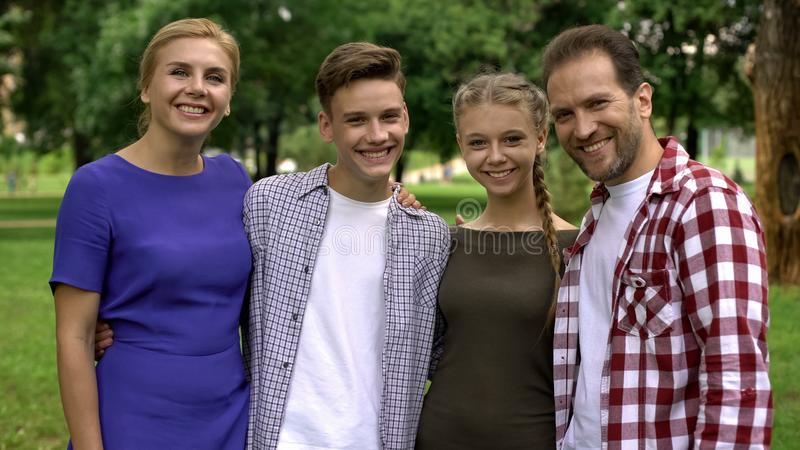Gelukkige familie die en in park koesteren glimlachen, die in camera, trots voor kinderen stellen royalty-vrije stock afbeelding