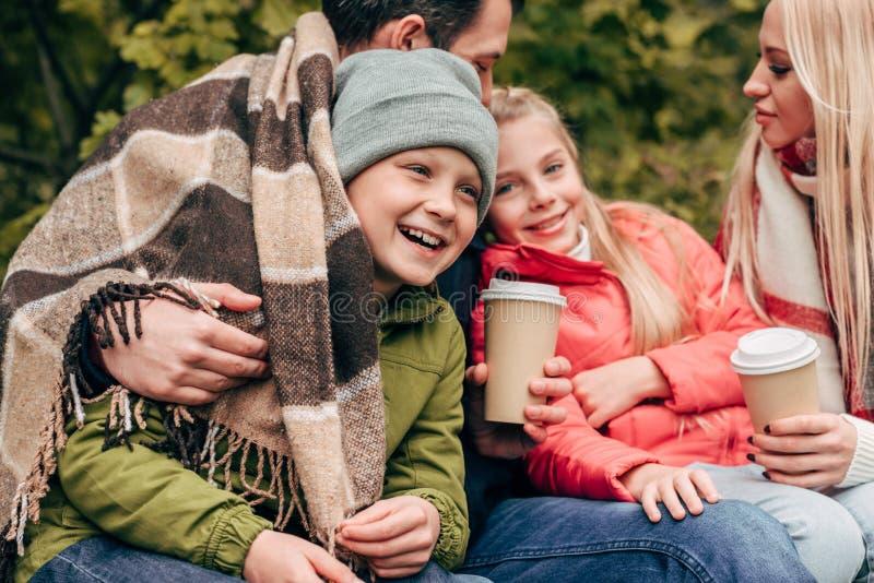 gelukkige familie die en van document koppen koesteren drinken royalty-vrije stock afbeeldingen