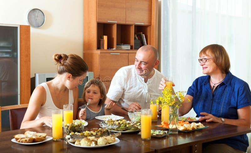 Gelukkige familie die gezond diner met vissen hebben thuis samen stock afbeeldingen