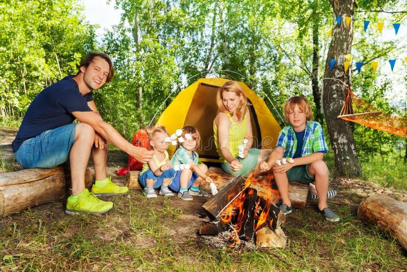 Gelukkige familie die heemst op roosteren stokken stock fotografie