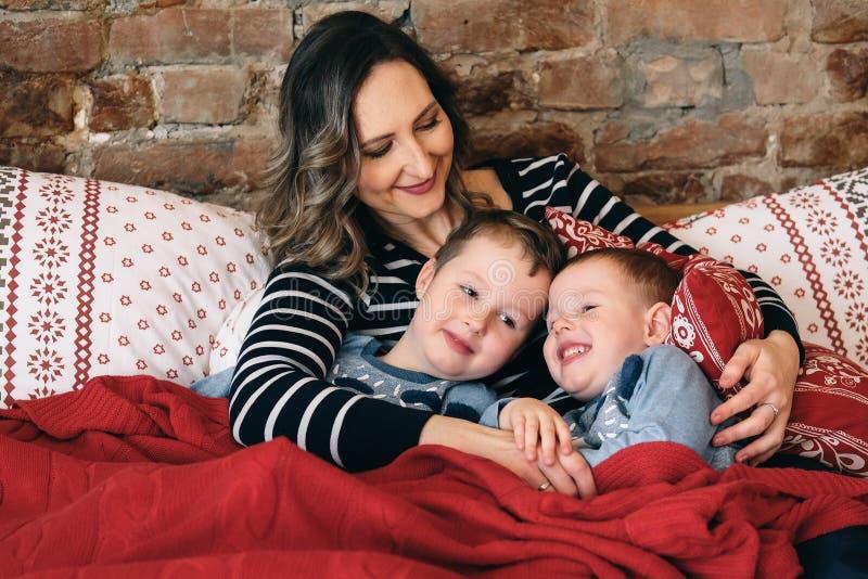 Gelukkige familie die in hun bed omhelzen stock afbeelding