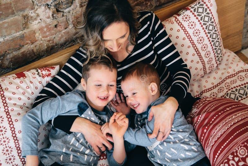 Gelukkige familie die in hun bed omhelzen royalty-vrije stock afbeeldingen
