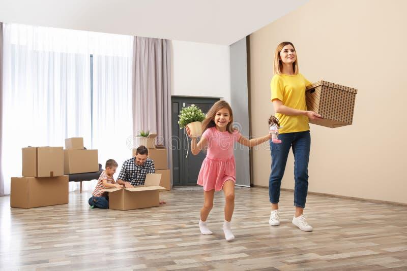 Gelukkige familie die hun bezittingen uitpakken dichtbij stapel van het bewegen van dozen royalty-vrije stock fotografie