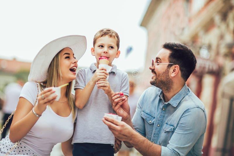 Gelukkige familie die hun weekend met zoon doorbrengen Zij eten het roomijs stock fotografie