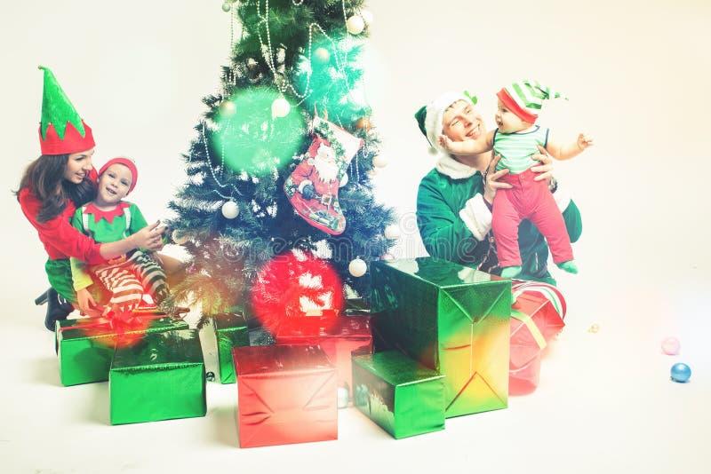 Gelukkige familie die Kerstboom, gekleed in elfkostuums verfraaien royalty-vrije stock afbeeldingen
