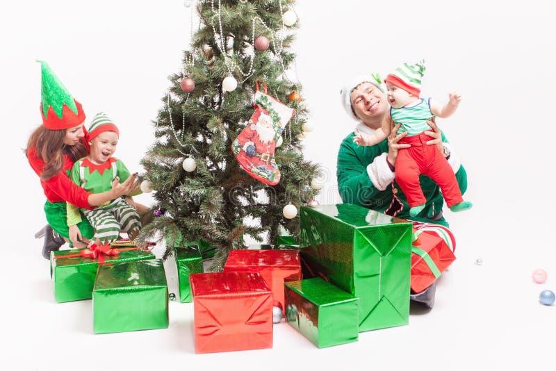 Gelukkige familie die Kerstboom, gekleed in elfkostuums verfraaien stock foto's