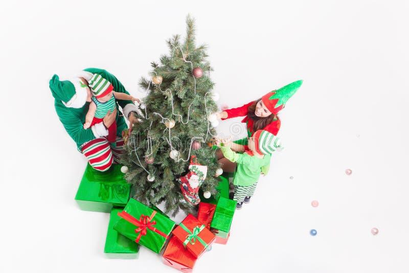 Gelukkige familie die Kerstboom, gekleed in elfkostuums verfraaien stock afbeelding