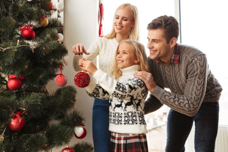 Gelukkige familie die Kerstmisboom thuis verfraaien stock fotografie
