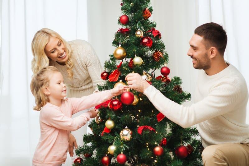 Gelukkige familie die Kerstmisboom thuis verfraaien stock foto's