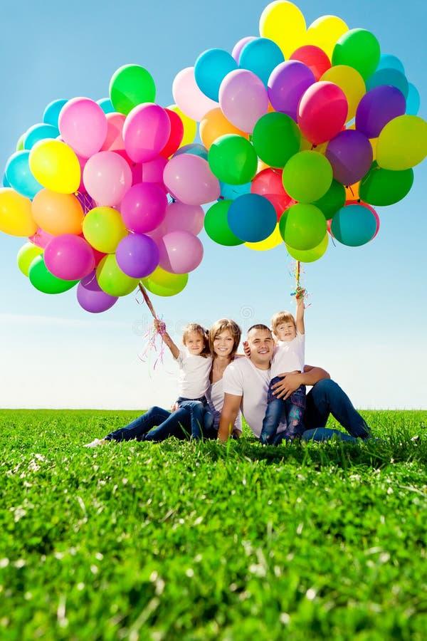 Gelukkige familie die kleurrijke ballons houden. Mamma, ded en daughte twee stock afbeelding