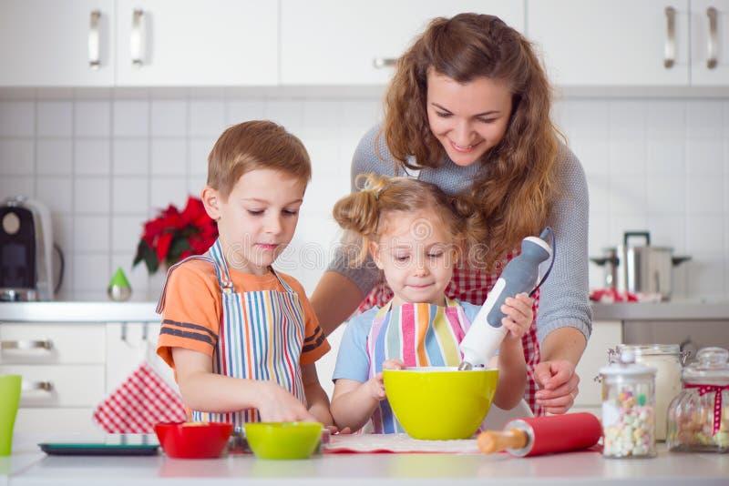 Gelukkige familie die koekjes voor Kerstmisvooravond voorbereiden stock foto's