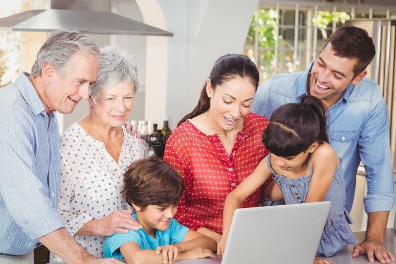 Gelukkige familie die laptop met behulp van royalty-vrije stock afbeelding