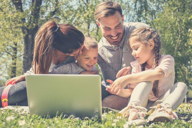 Gelukkige familie die laptop met behulp van, die op het groene gras zitten Familieen royalty-vrije stock foto's