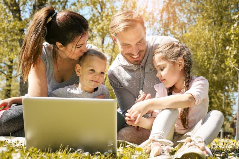 Gelukkige familie die laptop met behulp van, die op het groene gras zitten Familieen royalty-vrije stock foto