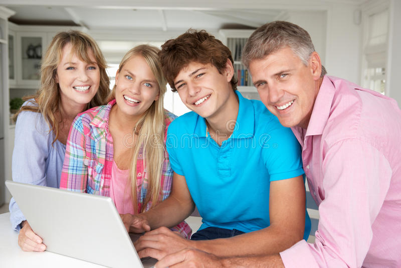 Gelukkige familie die laptop samen met behulp van stock foto's