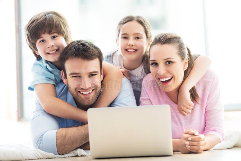 Gelukkige familie die laptop samen met behulp van royalty-vrije stock fotografie