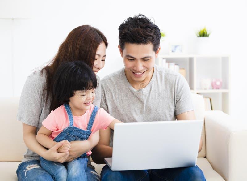 Gelukkige familie die laptop in woonkamer met behulp van stock afbeelding