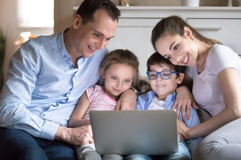 Gelukkige familie die met jonge geitjes op grappige video op het computerscherm letten stock foto's