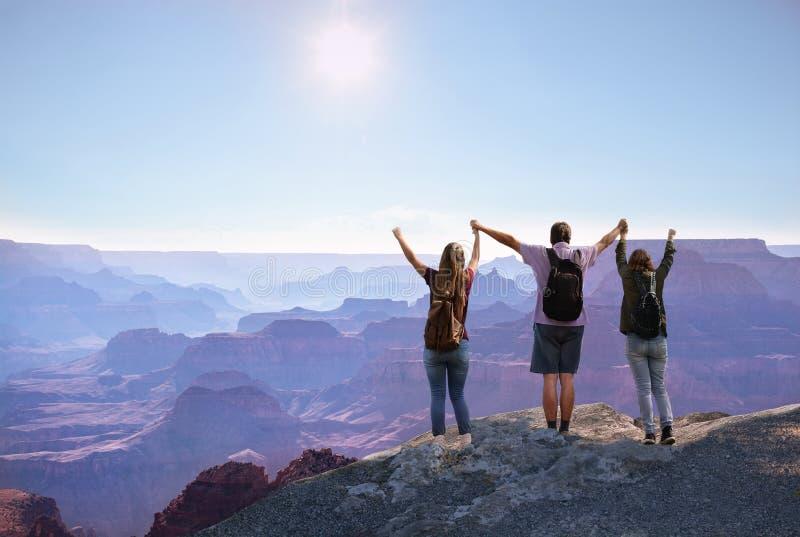 Gelukkige familie die met opgeheven handen van tijd samen bovenop de berg genieten royalty-vrije stock foto