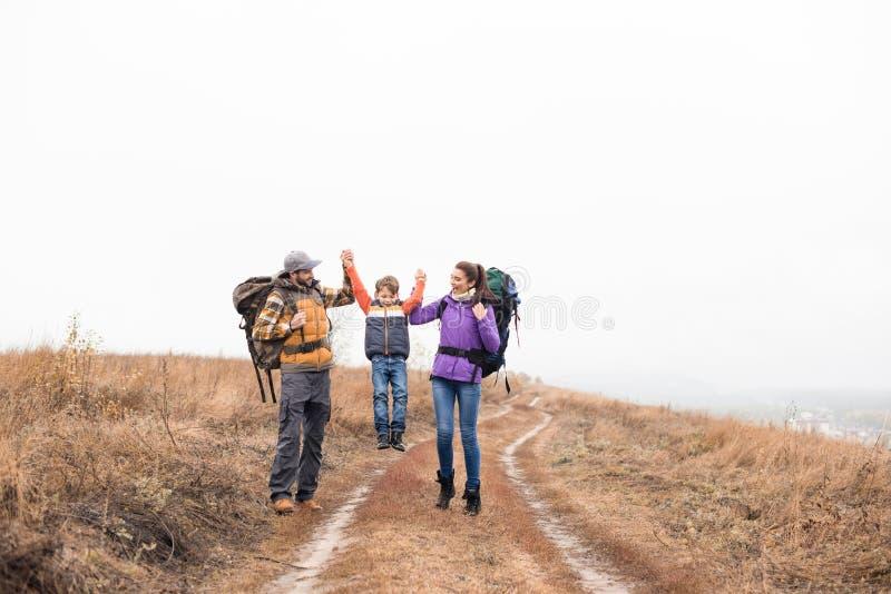 Gelukkige familie die met rugzakken handen houden stock foto