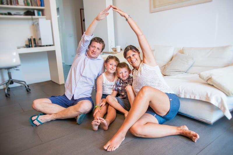 Gelukkige familie die met twee jonge geitjes op vloer zitten die dakcijfer met handen maken stock foto