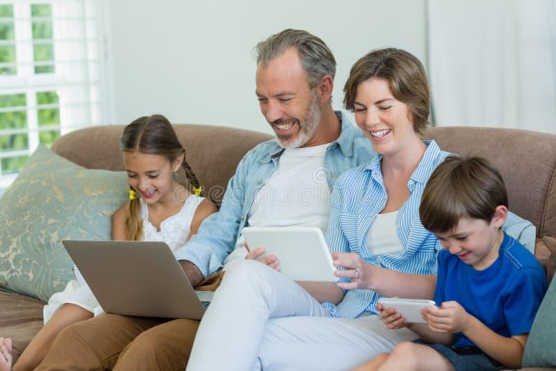 Gelukkige familie die mobiele telefoon, digitale tablet en laptop in woonkamer met behulp van stock afbeeldingen