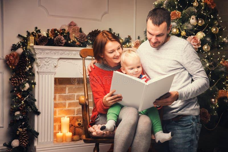 Gelukkige familie die onder Kerstmisdecoratie verhaal in een boek lezen stock foto's